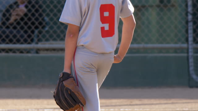 boys playing in a little league baseball game shortstop infielder wearing 9 and a red hat. - 野球用グローブ点の映像素材/bロール