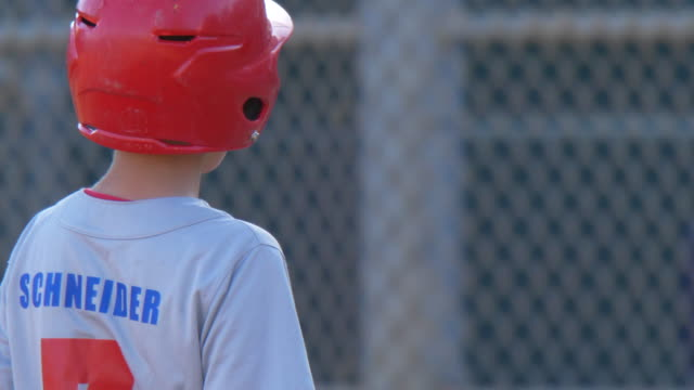 boys playing in a little league baseball game with a red batting helmet. - slow motion - goodsportvideo stock videos and b-roll footage