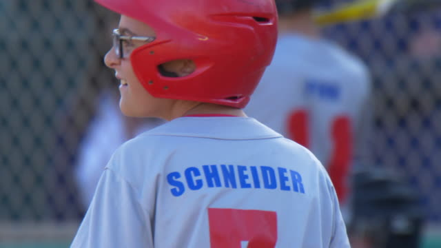 Boys playing in a little league baseball game with a red batting helmet. - Slow Motion