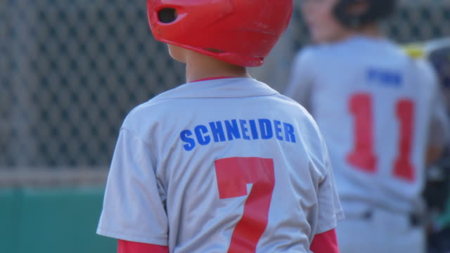 boys playing in a little league baseball game with a red batting helmet. - slow motion - zahl 7 stock-videos und b-roll-filmmaterial
