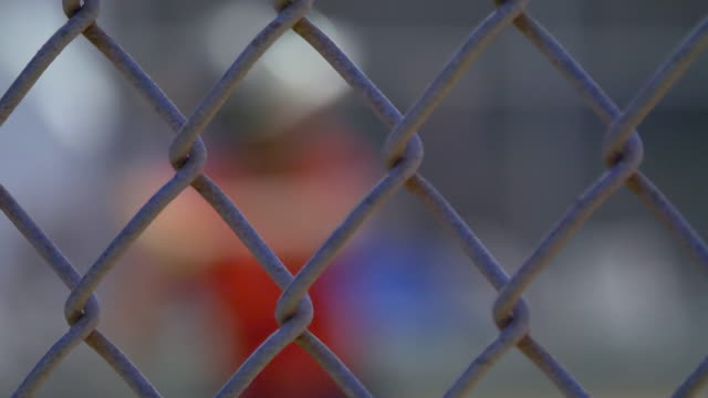 boys playing little league baseball game chain link fence. - slow motion - chainlink fence stock videos and b-roll footage