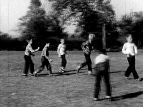 1950 boys playing pick-up game of football in park / usa / audio - anno 1950 video stock e b–roll