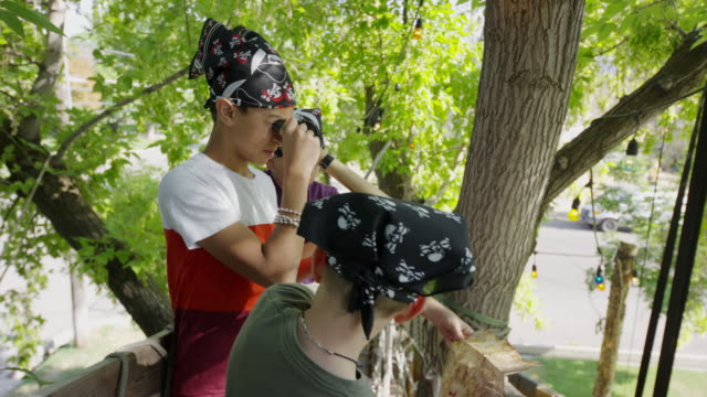 Boys playing pirate in tree searching with telescope / Provo, Utah, United States