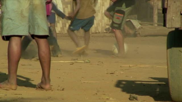 ms boys playing soccer in village, pak ou villages, laos - 裸足点の映像素材/bロール