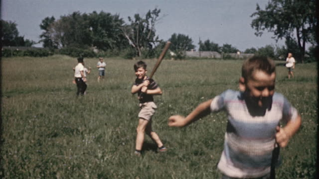1956 montage boys playing softball in field / usa - baseball bat stock videos & royalty-free footage