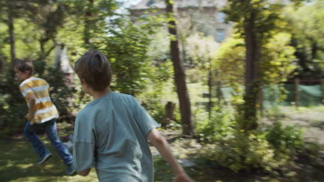 boys playing tag in backyard - playing tag stock videos & royalty-free footage