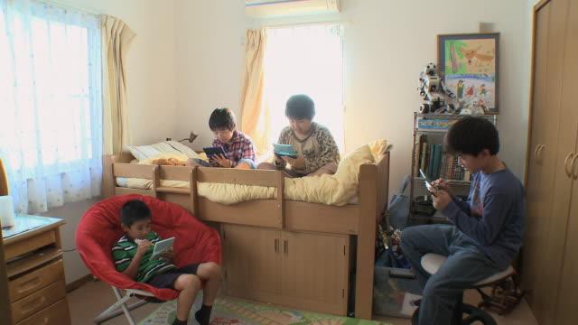 vídeos y material grabado en eventos de stock de ws td boys (8-9) playing video game in kids room / tokyo, japan - juego electrónico de bolsillo