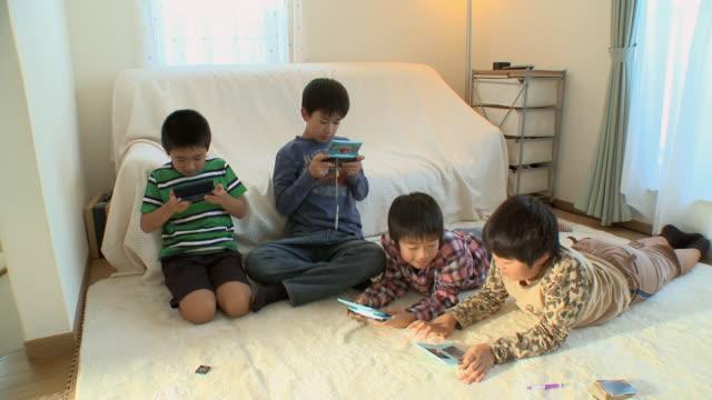 vídeos y material grabado en eventos de stock de ws boys (8-9) playing video game in kids room / tokyo, japan - juego electrónico de bolsillo