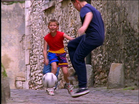 3 boys playing with soccer ball in street / paris - hamlet play stock videos and b-roll footage