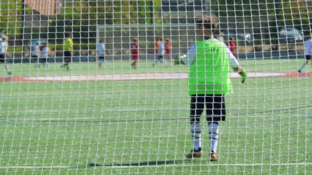 boys playing youth soccer football on a green turf grass field. - slow motion - ゴールポスト点の映像素材/bロール