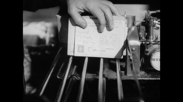 stockvideo's en b-roll-footage met montage a boy's postcard from manchester is brought to the post office, where it is sorted and begins its journey to sussex / manchester, england, united kingdom - 1938