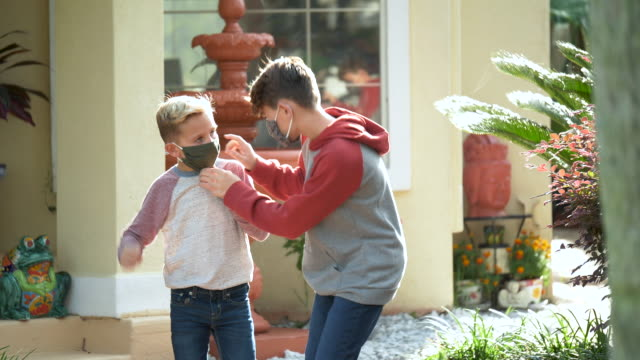 boys putting on face masks as they leave home - 8 9 years stock videos & royalty-free footage
