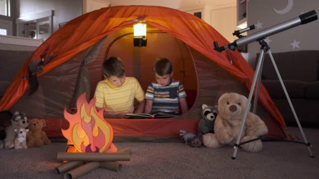 vídeos de stock e filmes b-roll de boys reading while camping indoors - aluno da escola primária