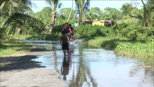 boys ride bicycles along flooded road after tidal flood, tuvalu - pacific ocean stock videos & royalty-free footage