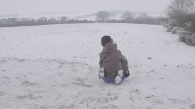 boys ride sledge down snowy slope, oxfordshire, england - sledge stock videos & royalty-free footage