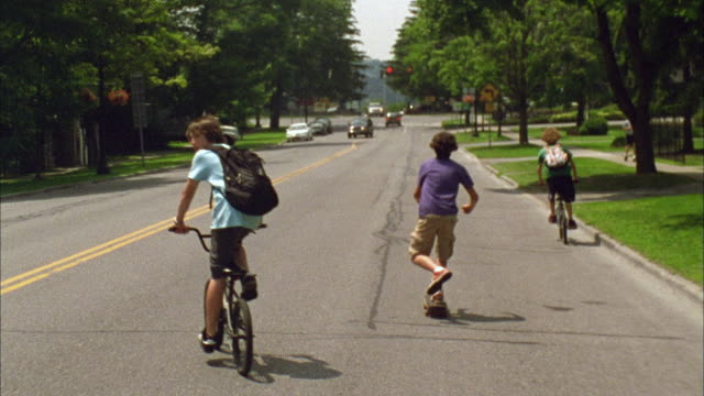ws ts boys riding bikes and skateboarding down road / cazenovia, new york, usa - drei personen stock-videos und b-roll-filmmaterial