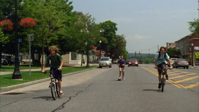 vidéos et rushes de ws ts pan zi boys riding bikes and skateboarding down road / cazenovia, new york, usa - quartier résidentiel