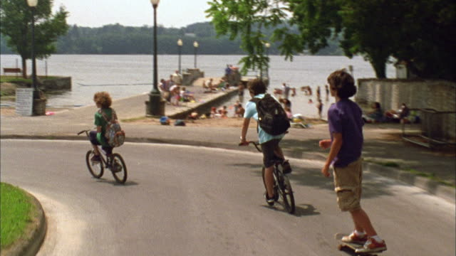 vídeos de stock, filmes e b-roll de t/l ws ts boys riding bikes and skateboarding down road to lake / cazenovia, new york, usa - cultura americana