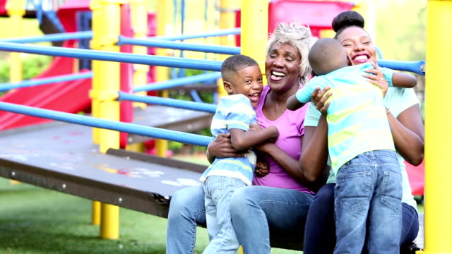 Boys run to their mother and grandmother on playground