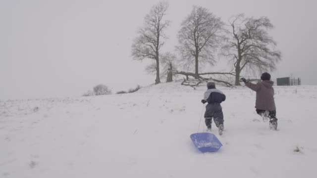 boys run with sledge over snow, oxfordshire, england - snow stock videos & royalty-free footage