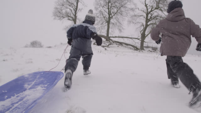 Boys run with sledge over snow, Oxfordshire, England