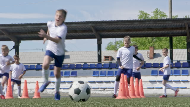 Boys running between orange cones on outdoor stadium