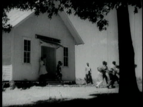 1940 montage boys running from building into woods / united states - 分校点の映像素材/bロール