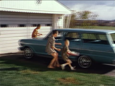 stockvideo's en b-roll-footage met 1962 pan boys running from house to station wagon as parents follow with beach gear / industrial - prelinger archief
