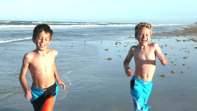 Boys running on sand and water at beach
