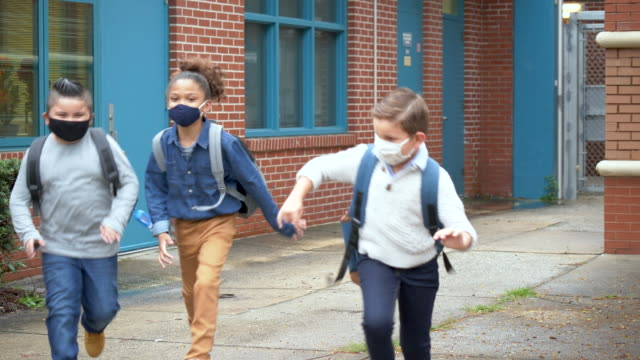boys running outside elementary school with face masks - 10 11 years stock videos & royalty-free footage