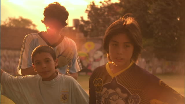 MS, PAN, boys (10-15) running with ball under arm on soccer field at sunset, Buenos Aires, Argentina