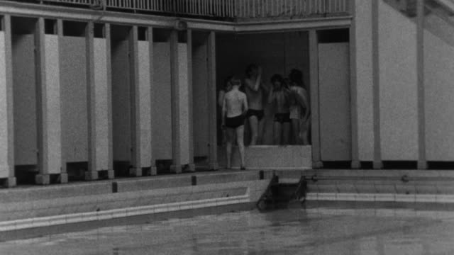 1976 B/W Boys showering at swimming pool while being watched by adult / Liverpool, Merseyside, England