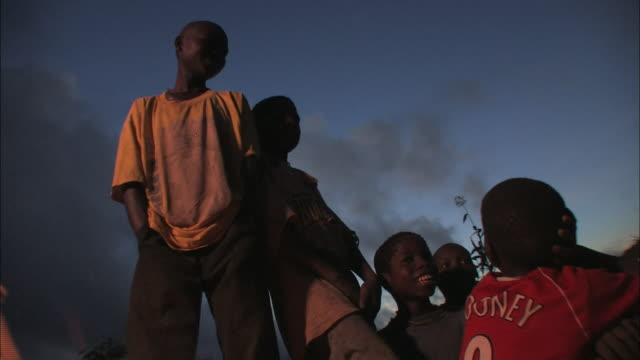 boys sit and stand by a small fire. - mozambique stock videos & royalty-free footage