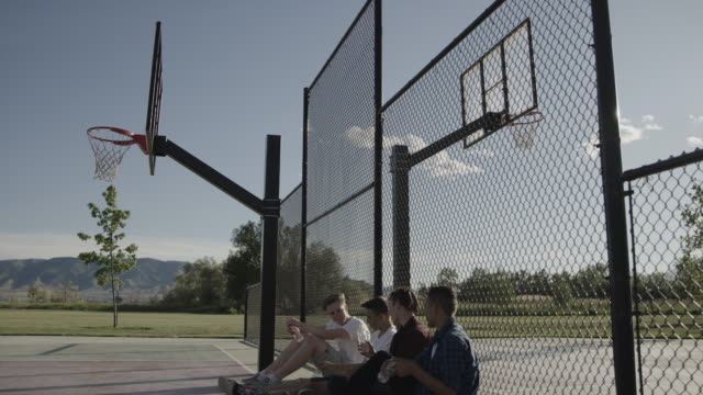 boys sitting against fence relaxing on basketball court drinking water / lehi, utah, united states - lehi stock videos & royalty-free footage