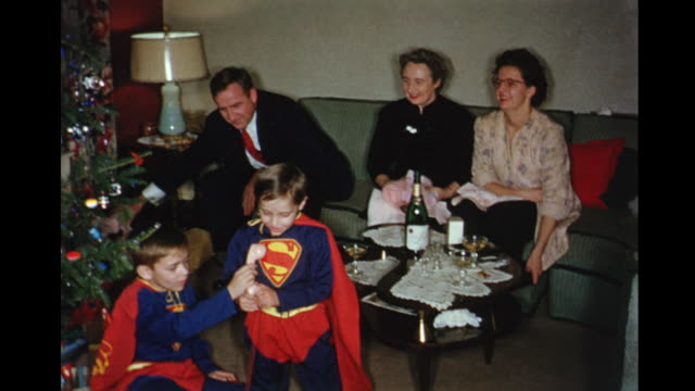 1956 home movie boys sitting beside christmas tree wearing superman outfits / adults sitting on sofa drinking / toronto, canada - 思い出点の映像素材/bロール