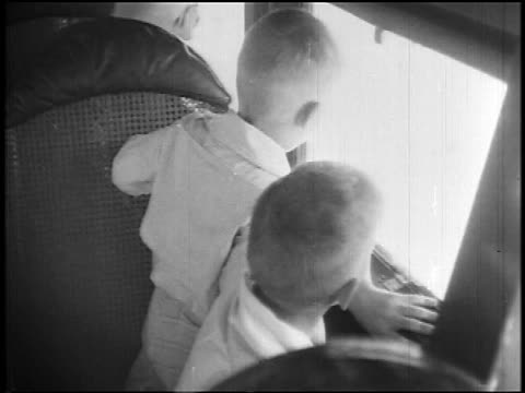 b/w 1927 2 boys sitting in airliner looking out of windows / newsreel - abitacolo video stock e b–roll