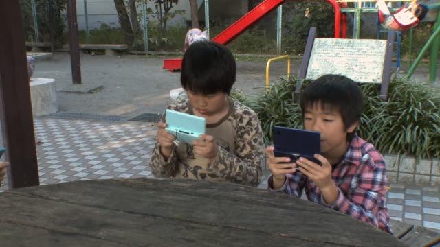 ms pan boys (8-9) sitting on bench playing video game at kids park / tokyo, japan - handheld video game stock videos & royalty-free footage