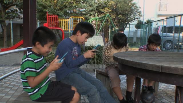 ms boys (8-9) sitting on bench playing video game at kids park / tokyo, japan - handheld video game stock videos & royalty-free footage