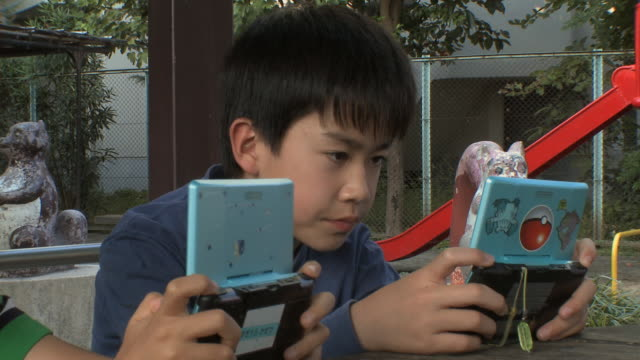 cu boys (8-9) sitting on bench playing video game at kids park / tokyo, japan - handheld video game stock videos & royalty-free footage