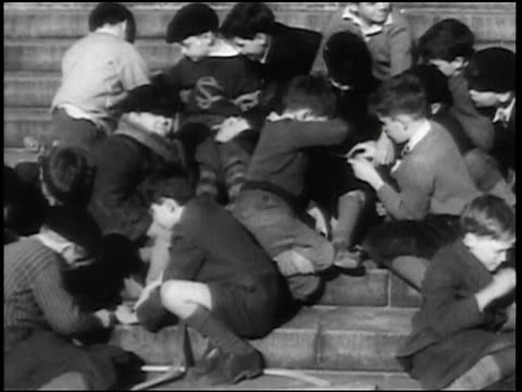 b/w 1938 boys sitting on steps outside playing with jigsaw puzzles / newsreel - jigsaw puzzle stock videos & royalty-free footage