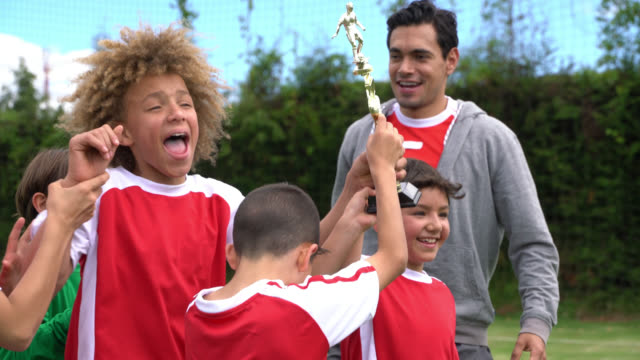 boys soccer team and coach celebrating they won the tournament holding the trophy and jumping excited - males stock videos & royalty-free footage