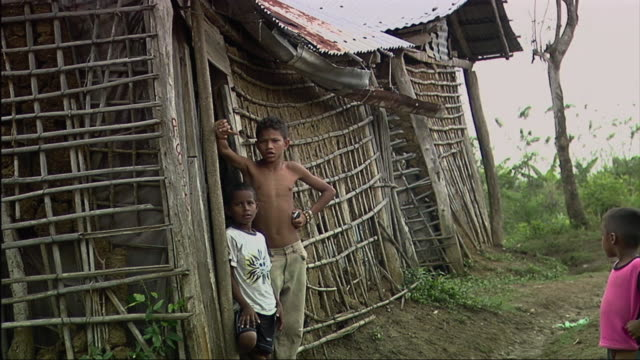stockvideo's en b-roll-footage met ms boys standing in front of hut / colombia - handen op de heupen