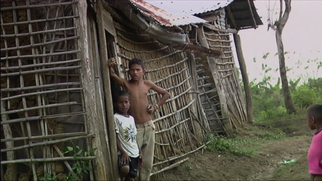 ms boys standing in front of hut / colombia - hand an der hüfte stock-videos und b-roll-filmmaterial
