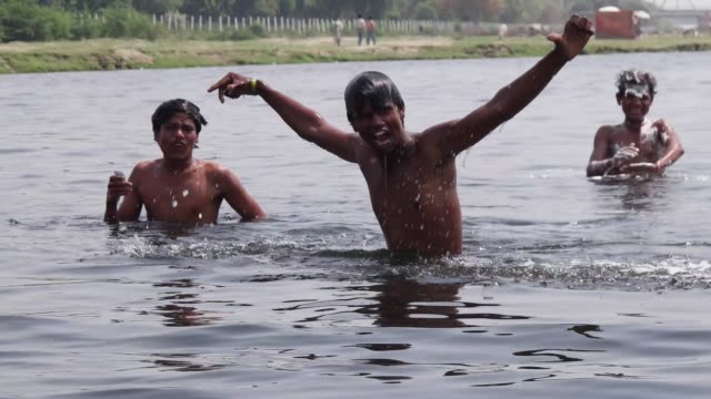 Boys swimming in river Yamuna / The term ghat refers to a series of steps leading down to a body of water particularly a holy river This is such a...