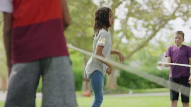 vídeos de stock, filmes e b-roll de boys swinging jumping rope for girl in playground / provo, utah, united states - provo