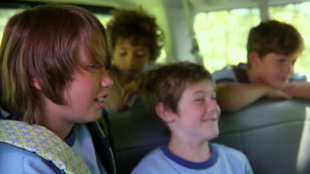 vídeos de stock, filmes e b-roll de ms, r/f, pan, boys (8-11) talking and giggling sitting in van, bovina, new york state, usa - mãos cobrindo boca