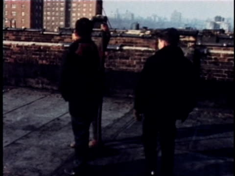 vídeos de stock e filmes b-roll de 1968 montage boys talking on rooftop of apartment building, new york city, new york, usa, audio - 1968