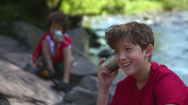 MS, R/F, boys (8-9) talking on tin can phone sitting on rocks, Bovina, New York State, USA