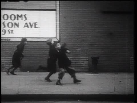 b/w 1939 boys throwing objects on city sidewalk + running away / nyc / documentary - 公共物破壊点の映像素材/bロール