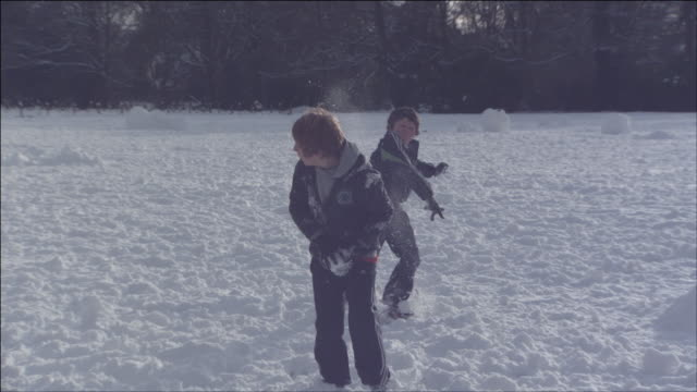 boys throwing snowballs at each other - geschwister stock-videos und b-roll-filmmaterial